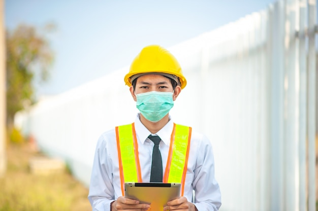 Asian man engineer face mask holding mobile phone device technology work on site construction