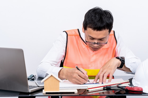 Asian man engineer sitting at a glass table drqwing a sketvh of the project