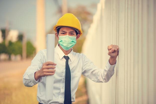 アジア人男性エンジニアは青写真検査建設ビル不動産を保持しているフェイスマスク黄色のヘルメットを使用します。