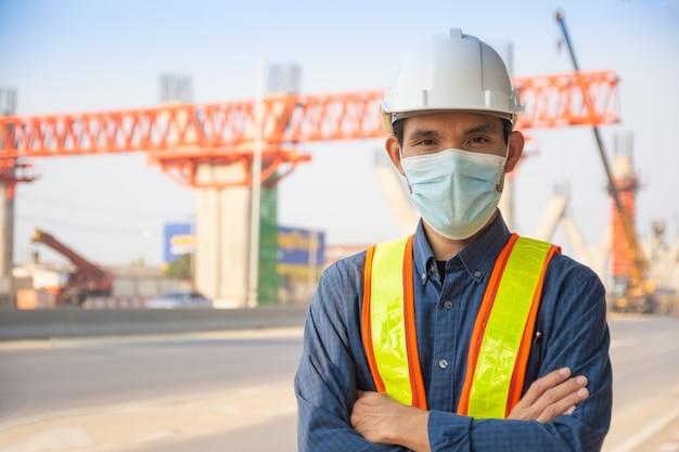 사이트 건설에 아시아 남자 엔지니어 작업자 안면 마스크 서, 건축 안전모는 노동자 통제를 보호합니다