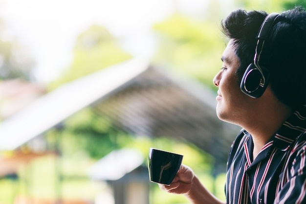 An asian man enjoy listening to music with headphone while drinking coffee