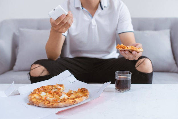 自宅でテレビを見ながらソファに座ってピザを楽しんでいるアジア人男性。