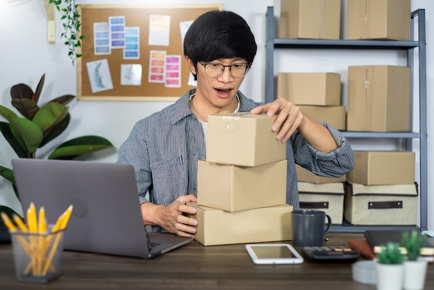 Asian man entrepreneur startup small business entrepreneur sme freelance man working with box to online marketing packaging and delivery scene at home office, onlinebusiness seller concept.