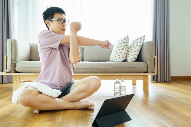 居間で運動し、デジタルタブレットを探しているアジア人男性