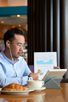 Asian man explaining data in business document to his business partner on a video call