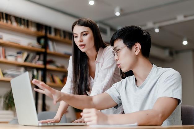 Asian man explains laptop science to female secretary