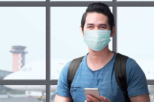 Asian man in the face mask with a backpack holding smartphone on the airport terminal. traveling in the new normal