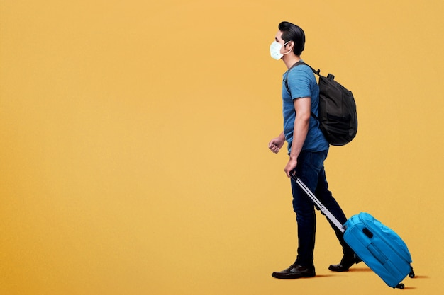 Asian man in the face mask with backpack and suitcase. traveling in the new normal