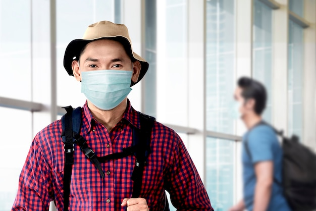 Asian man in the face mask with hat and a backpack on the airport terminal. traveling in the new normal