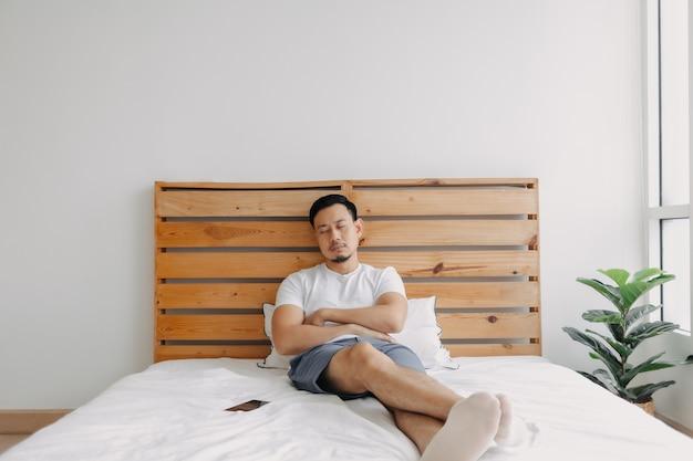 アジア人男性が携帯電話を手にベッドで眠りに落ちる