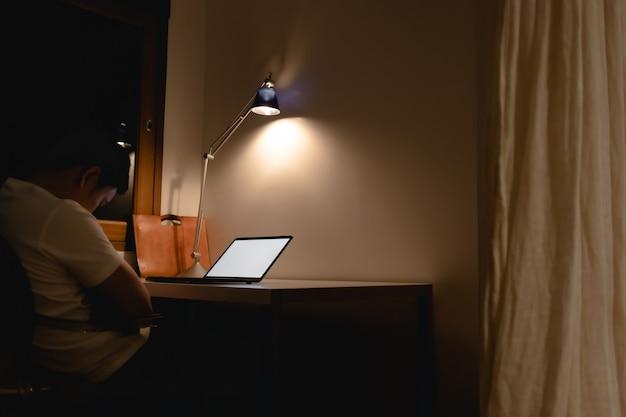 아시아 남자는 밤에 노트북으로 책상에서 작업하는 동안 잠에 빠진다.