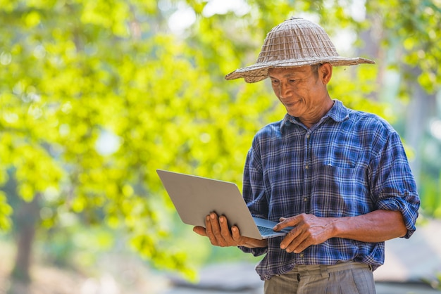Asian man farmer with laptop outside