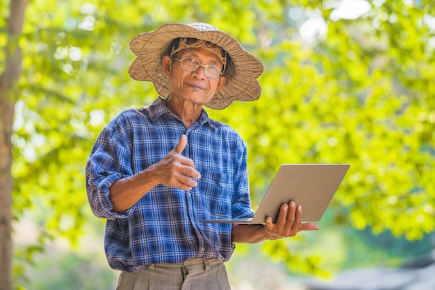 Asian man farmer with smart phone and laptop business and technology concept,asian man farmer on empty copy space