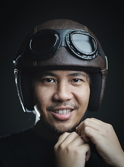 Asian man fastening his retro helmet