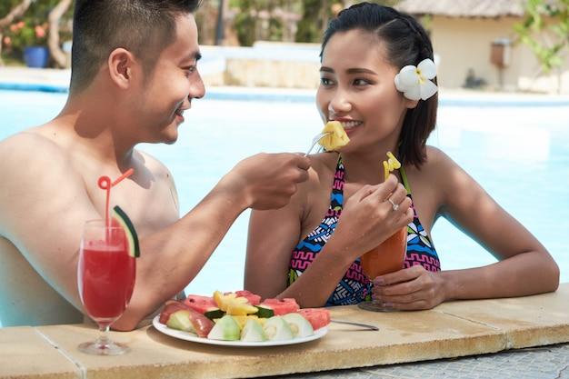 アジア人男性のガールフレンドに餌をやるトロピカルリゾートでフルーツをスライス