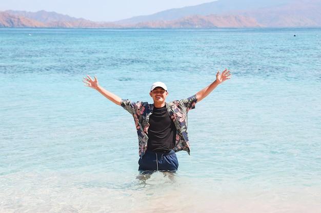 Asian man feeling free and enjoying vacation on the beach
