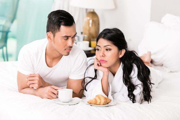 Азиатский мужчина чувствует себя отвергнутым его женой на кровати