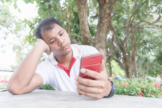 Asian man feels bored and sad moment with mobile phone. he wait something from mobile.
