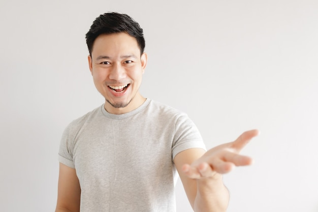 Asian man feels excited. the man wears grey t-shirt on grey wall.