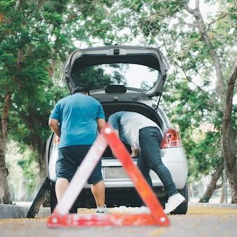 Азиатский мужчина находит инструменты в машине для ремонта автомобиля после поломки автомобиля на улице.