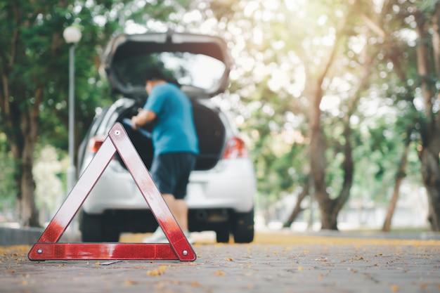 アジア人男性が路上で車が故障した後、車の修理のために車の中でツールを見つける