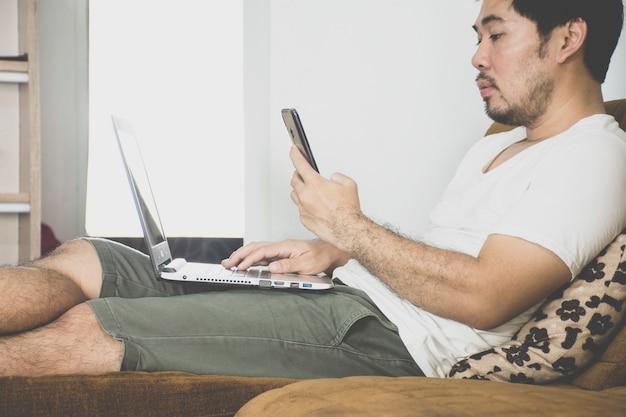 Работа азиатского человека независимая от дома используя компьтер-книжку и smartphone на софе ткани, эффект coronavirus, covid-19.