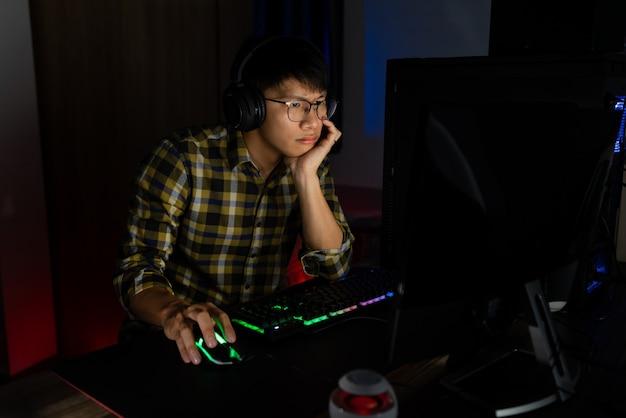 手でストレスを感じているヘッドフォンのアジア人男性ゲーマーは、コンピューターでビデオゲームを失うと、落ち込んだり怒ったりショックを受けたりします。間違い、ビデオゲームテクノロジー、eスポーツのコンセプトに対する恐怖と動揺。