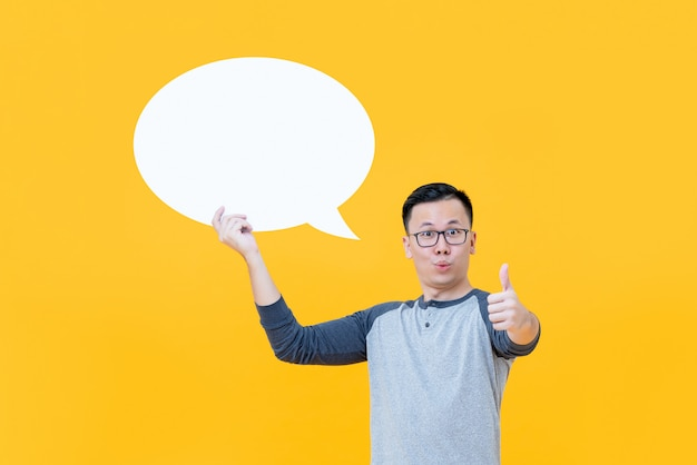 Asian man giving thumbs up while holding blank speech bubble