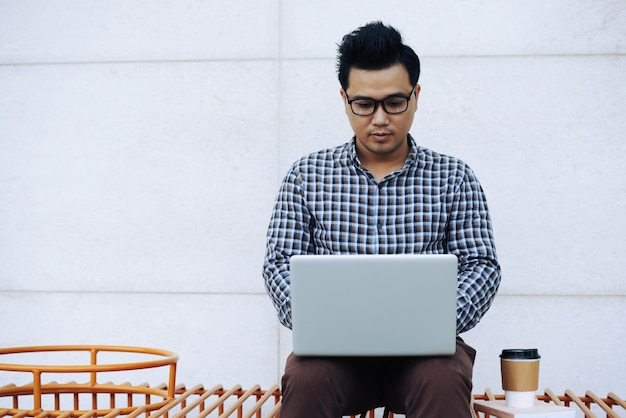 Asian man in glasses sitting on bench outdoors and working on laptop