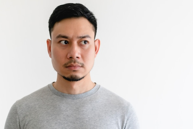 Asian man in a grey t-shirt is looking at the empty space on isolated white background.