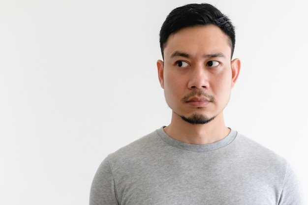 Asian man in a grey t-shirt is looking at side isolated