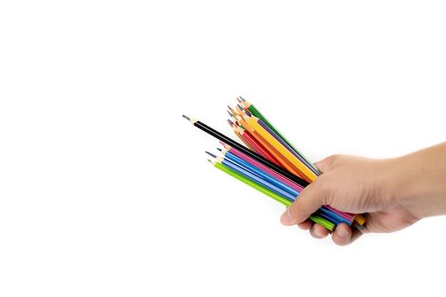 Азиатская мужская рука держит в руке много цветных карандашей, возглавляемых черным цветным карандашом на белом фоне. отсечения путь.