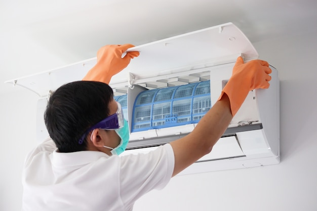 Азиатский мужчина держит концепцию очистки фильтра кондиционера