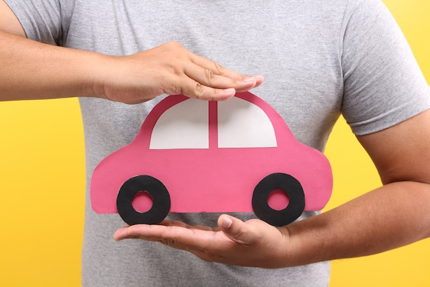 Asian man hand hold red paper car shape on yellow background in studio. protection of car concept.