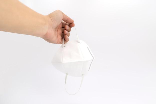 アジア人の手は白い背景の上のスタジオライトで白いクリアpmマスクを保持します