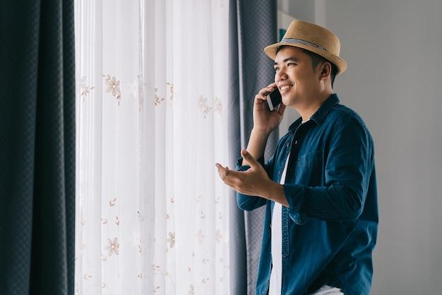 アジア人男性は、窓際のスマールフォンで楽しく商売をしています。