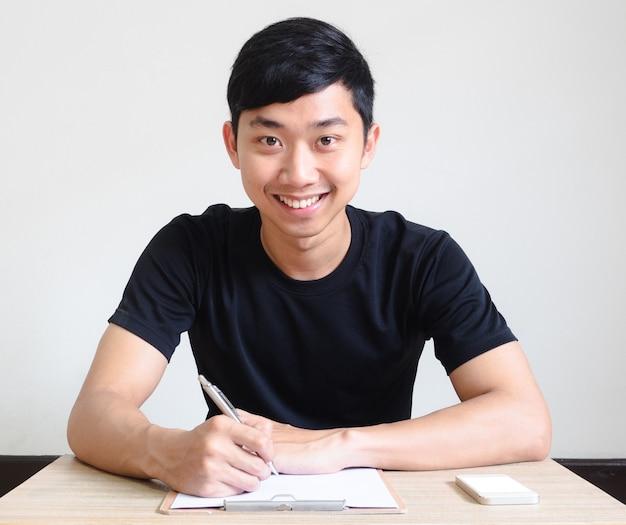 아시아 남자 행복한 미소는 체크리스트와 휴대전화 인터뷰 컨셉으로 책상에 앉아 있다