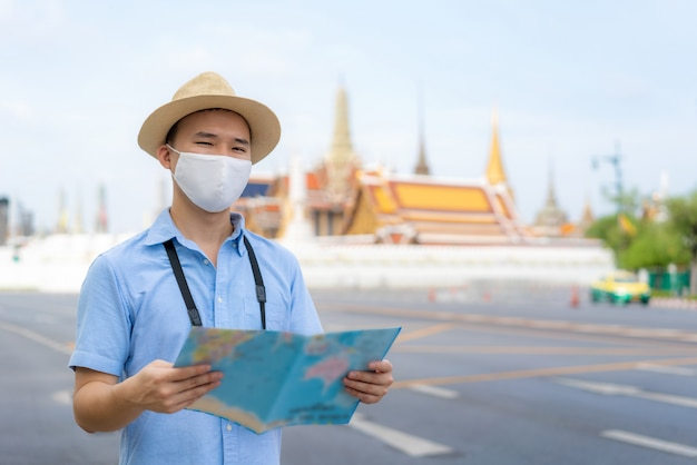 Asian man happy tourists to travel wearing mask
