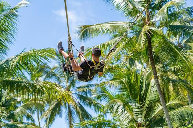ジャングルの中でスイングを楽しんでいるアジア人男性。インドネシア、ウブド近郊の田んぼにあるバリ島の熱帯雨林で揺れる人々