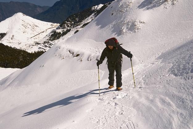 屋外で氷雪の白い道をハイキングするアジア人男性。