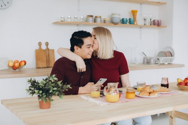 Asian man and his caucasian blonde woman have breakfast. they spend time together in kitchen and look video on the phone.
