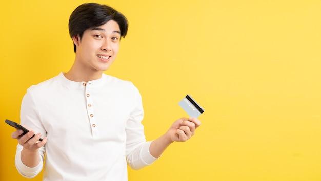 그의 손에 은행 카드를 들고 아시아 남자