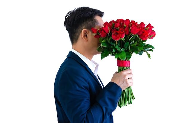Азиатский мужчина держит букет красных роз на день святого валентина концепции.