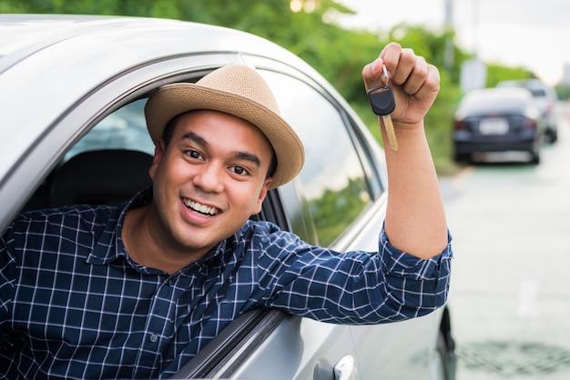 車に座っている間車のキーを保持しているアジア人