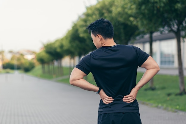 Азиатский мужчина сдерживает боль в спине после бега и фитнеса