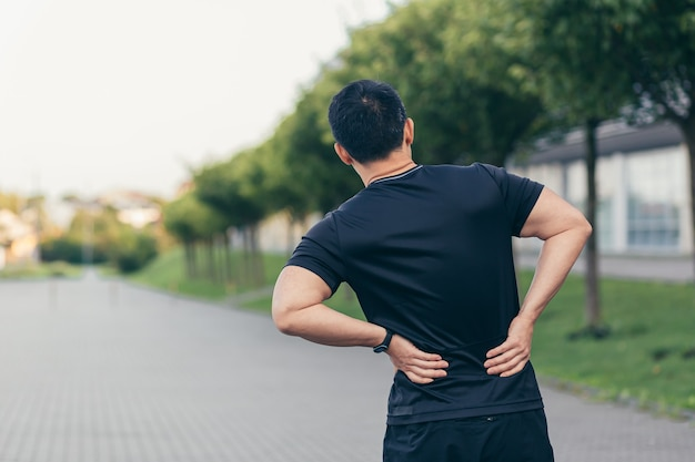 Asian man holding back pain after running and fitness