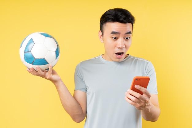 手にボールと電話を保持しているアジア人男性
