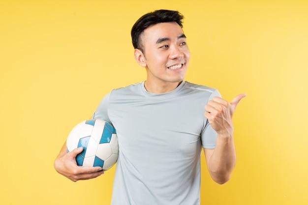 ボールを保持し、ポインティングアジア人男性