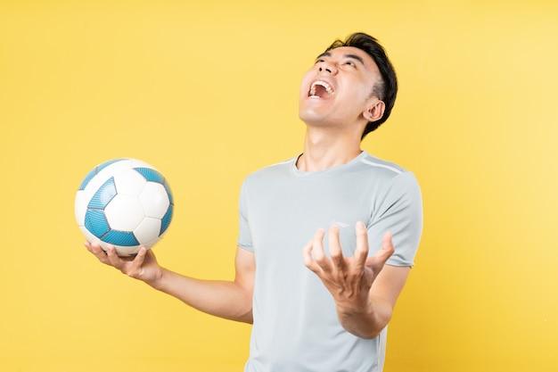 手にボールを持って叫んでいるアジア人男性
