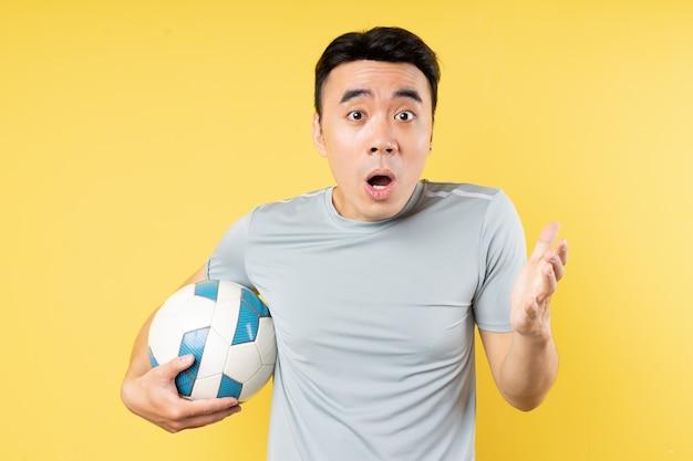 驚きの表情でボールを保持しているアジア人男性